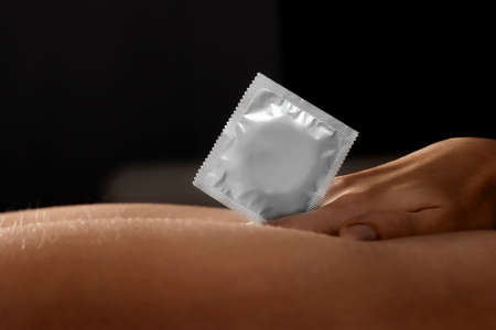 Close-up of a condom in a female hand. Sexual foreplay, contraception, safe sex concept, venereal disease protection