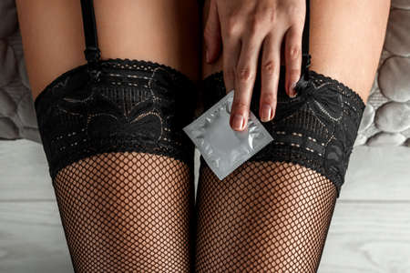 Condom in a female hand against the background of sexy legs in black stockings. Sexual foreplay, contraception, safe sex concept, venereal disease protection