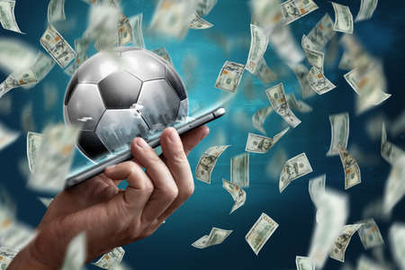 Online sports betting. Dollars are falling on the background of a hand with a smartphone and a soccer ball. Creative background, gambling