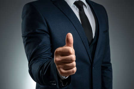 Male hand in suit shows thumbs up gesture on gray background. Concept ok, approval, close-up