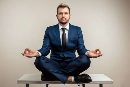 A businessman in a blue suit at a work table. Meditation at work. Emotional work. Multitasking, effective business worker concept