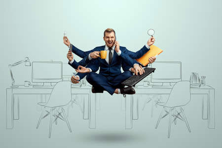 A businessman with many hands in a suit levitates in the office. Works simultaneously with several subjects. Multitasking, efficient business worker concept
