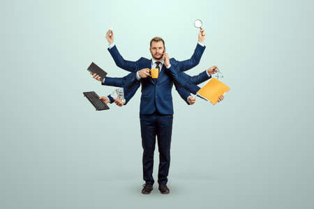 Businessman with many hands in a suit. Works simultaneously with several objects, a mug, a magnifying glass, papers, a contract, a telephone. Multitasking, efficient business worker concept 스톡 콘텐츠