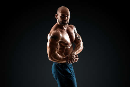 Male bodybuilder with light stubble with a torso posing against a dark background. The concept of a fitness club, doing sports, weightlifting. Copy space Foto de archivo