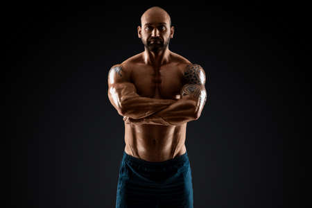 Male bodybuilder with light stubble with a torso posing against a dark background. The concept of a fitness club, doing sports, weightlifting. Copy space