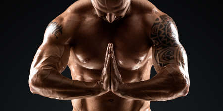 Male bodybuilder with light stubble and torso shows muscularity against a dark background. The concept of a fitness club, doing sports, weightlifting. Copy space