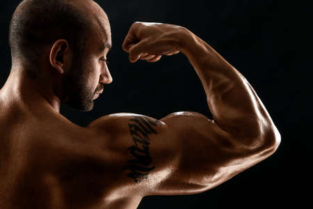 Male bodybuilder with light stubble and torso shows muscularity against a dark background. The concept of a fitness club, doing sports, weightlifting. Copy space Banque d'images