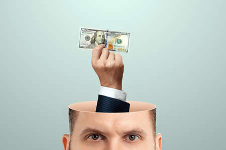 Business thinking, a hand with a banknote, dollars, sticks out of the man's head instead of the brain. Creative background, business concept, profitable idea, startup 스톡 콘텐츠