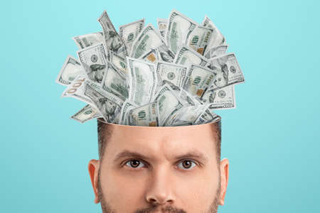 Business thinking, money, dollars sticking out of the mind of a man instead of a brain. Creative background, business concept, entrepreneurship, startup