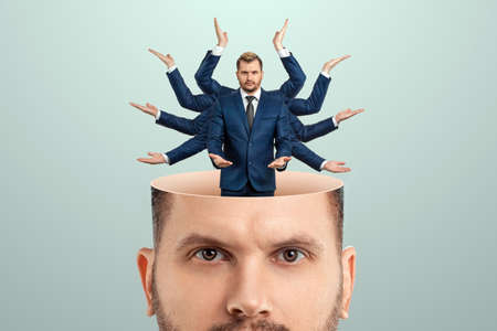Instead of a brain, a man has a multi-armed businessman in his head. Creative picture, concept of multitasking, multi-hands, brain work, stress resistance 스톡 콘텐츠