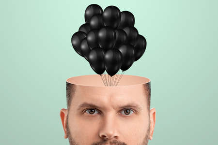 Close-up of a male head instead of a brain and an empty head balloons are flying out. Creative background