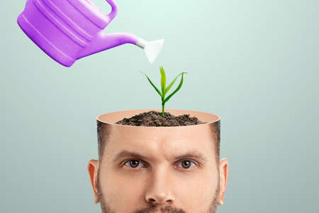 A fresh idea, a man's head is open hand watering the plant growing from the head. Creative background, brain, fantasy, creativity