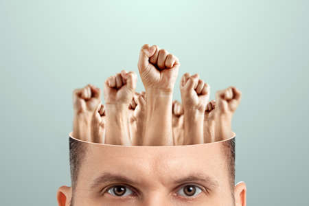 Close-up of a man's head instead of a brain, fists raised up. The concept of fighting for their rights, labor movement, electoral movement. Creative background