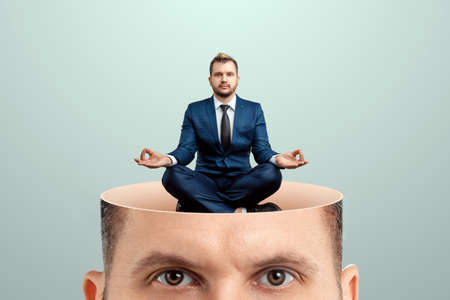 Rest for the brain, close-up of a man's head inside a man in a business suit sitting in the lotus position. Creative background, concept of reload, meditation, calmness, appeasement