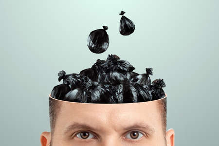 Trash in the head, a man's head is open instead of a brain trash bags. Creative background, unnecessary information, useless knowledge, wrong thinking