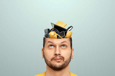 Rubbish in the head, a man's head is open instead of a brain, various office rubbish. Creative background, unnecessary information, useless knowledge, wrong thinking Standard-Bild