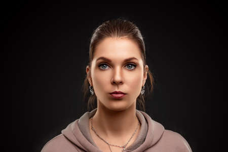 Portrait of a beautiful serious European girl, woman on a black background 스톡 콘텐츠