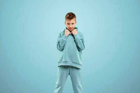 Little in a turquoise suit poses and fools around on a turquoise background, looks at the camera. Children's studio portrait. Childhood lifestyle concept