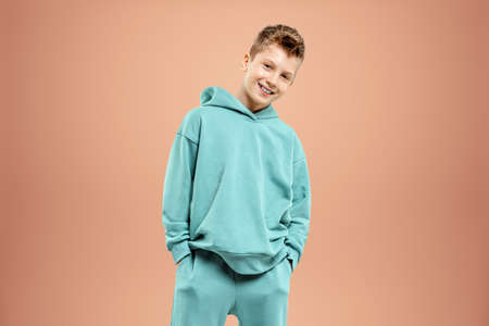 A boy in a turquoise suit posing and fooling around on a beige background, looking at the camera. Children's studio portrait. Childhood lifestyle concept