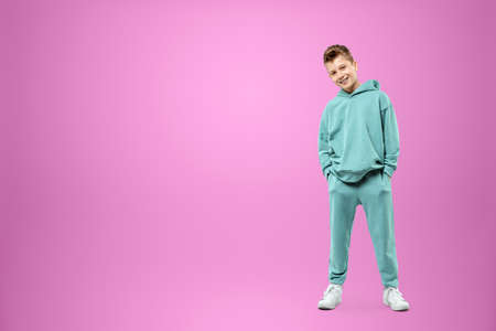 Little in a turquoise suit posing and fooling around on a pink background, looking at the camera. Children's studio portrait. Childhood lifestyle concept