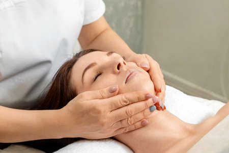 Facial massage close-up. Young, beautiful girl at spa procedures. Skin care, oriental massage treatments, beauty treatments