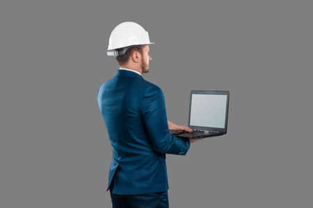 A man in a business suit, an architect with a white helmet on his head, holds a laptop, isolated on a white background. Architecture, construction concept Standard-Bild