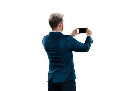 Man, Businessman in a business suit photographs something on a smartphone. concept Business online, remote work, freelance Standard-Bild