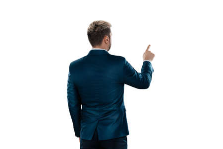 A man, a businessman in a business suit is isolated on a white background, points at something with his finger Standard-Bild
