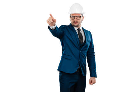 A man in a business suit, an architect with a white helmet on his head points his finger at something, isolated on a white background. Architecture, construction concept