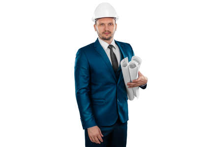 A man in a business suit, an architect with a white helmet on his head, holds blueprints, is isolated on a white background. The concept of architecture, construction, blueprints, plan Standard-Bild
