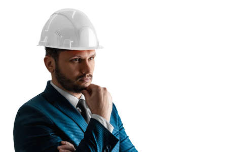 A man in a business suit, an architect with a white helmet on his head close-up, isolated on a white background. The concept of architecture, construction, blueprints, plan