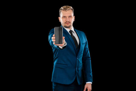 A man, a businessman in a business suit holds out a smartphone close-up, is isolated on a white background Standard-Bild