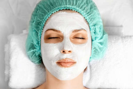 The girl's face covered with a cosmetic mask, close-up. Skin care, beautician, spa treatments, facial hygiene Фото со стока