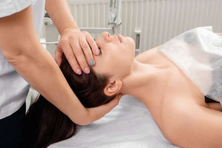 A massage is being done on the face of a beautiful girl, close-up. Skin care, beautician, spa treatments, facial hygiene