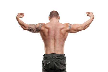 Tattooed male bodybuilder posing over white background. Fitness workout concept, muscle groups, watch your body