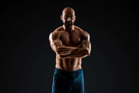 Tattooed male bodybuilder posing over black background. Fitness workout concept, muscle groups, watch your body