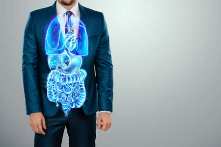 A holographic projection of a scan of human internal organs inside the body of a man in a suit. The concept of modern medicine, digital x-ray, new technologies, human anatomy