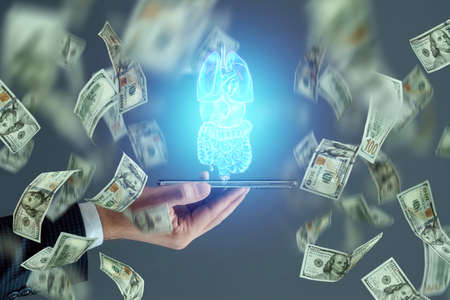 Holographic projection scan of human internal organs and dollars. The concept of the cost of modern medicine, expensive services of doctors, the cost of drugs