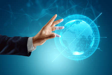 The businessman's hand reaches for the earth hologram. Globalization concept, business to the whole world, online business