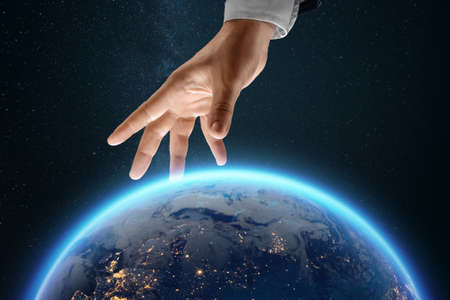 A businessman's hand reaches for the image of the earth from space. Globalization concept, business to the whole world, online business