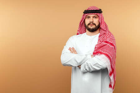 Arab man businessman in national clothes folded his arms on his chest, beige background. Dishdasha, kandora, thobe, middle east traditional menswear concept, islam. Copy space 免版税图像