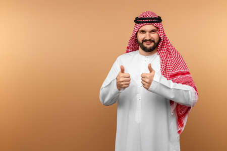 Arab man businessman in national clothes shows thumbs up, like, beige background. Dishdasha, kandora, thobe, middle east traditional menswear concept, islam. Copy space 免版税图像