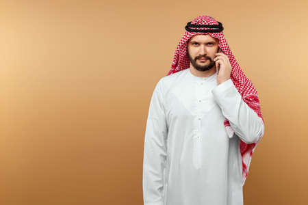 Arab man businessman in national clothes talking on a smartphone, like, beige background. Dishdasha, kandora, thobe, middle east traditional menswear concept, islam. Copy space 免版税图像