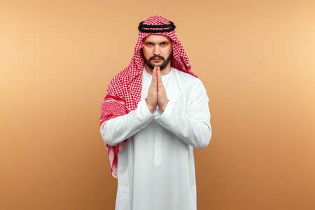 Arab man businessman in national clothes folded his hands in prayer, like, beige background. Dishdasha, kandora, thobe, middle east traditional menswear concept, islam. Copy space