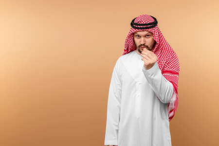 Arab man businessman in national dress holds a smartphone in his hands, beige background. Dishdasha, kandora, thobe, middle east traditional menswear concept, islam. Copy space