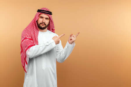Arab male businessman in national clothes points with his hands to something, Beige background. Dishdasha, kandora, thobe, middle east traditional menswear concept, islam. Copy space