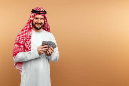 Arab man businessman in national clothes is holding dollars in his hands. Business concept in the middle east, oil sale, investment 免版税图像