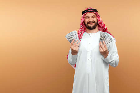 Arab man businessman in national clothes rejoices in dollars in his hands, great profit. Business concept in the middle east, oil sale, investment