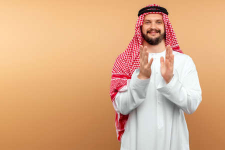 Arab male businessman in national clothes is applauding. Dishdasha, kandora, thobe, middle east traditional menswear concept, islam. Copy space