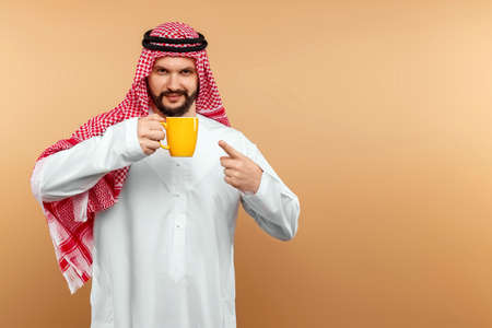 Arab man businessman in national dress holds a cup in his hands. Dishdasha, kandora, thobe, middle east traditional menswear concept, oriental hospitality. Copy space